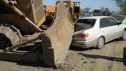 В результате падения бульдозера пострадало два автомобиля